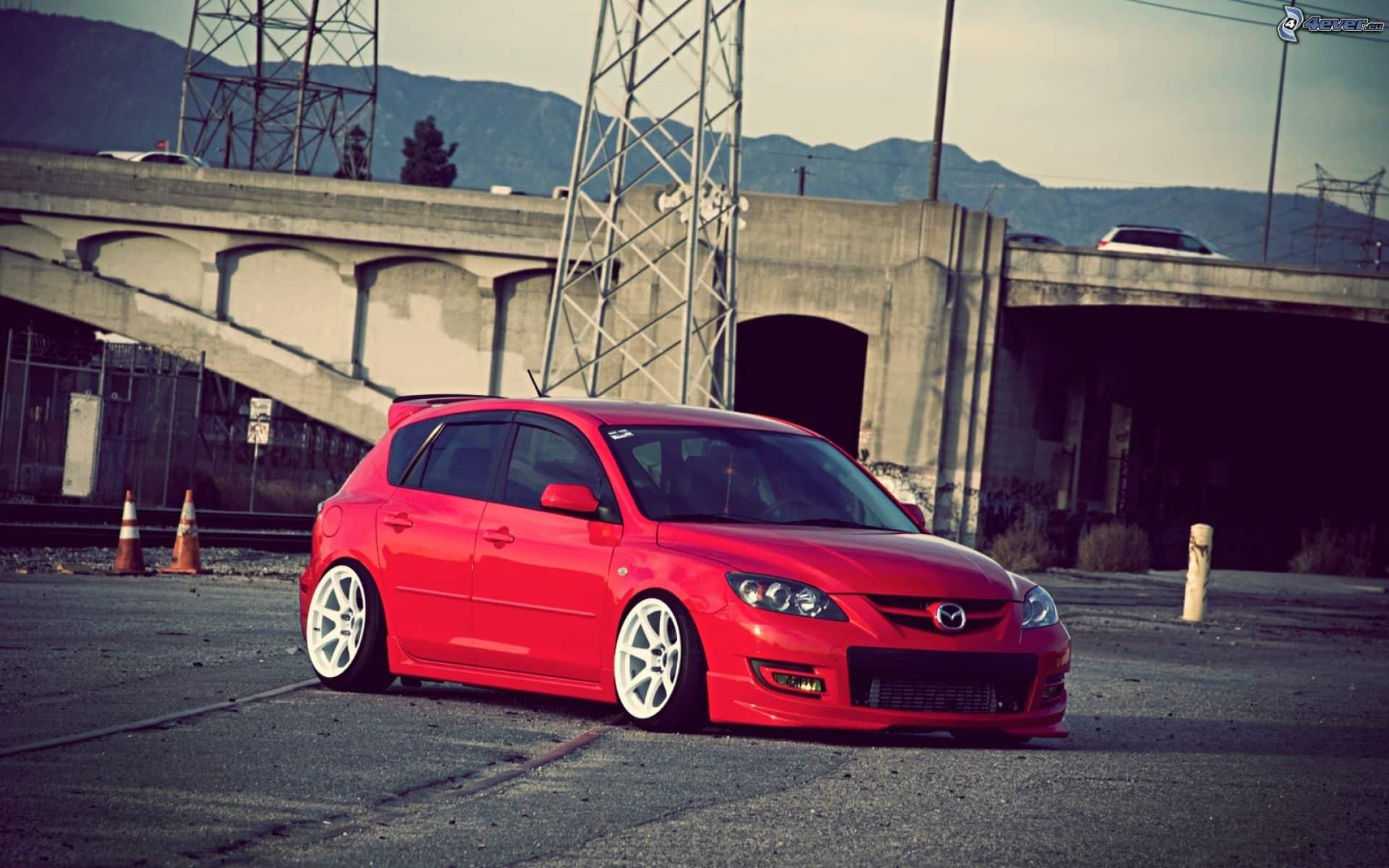 Красная Mazda 3 на фоне моста